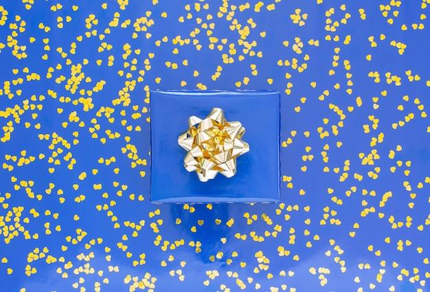 Geschenkbox mit einer goldenen schleife auf einem blauen hintergrund, goldene glänzende glitzerherzen auf einem blauen hintergrund