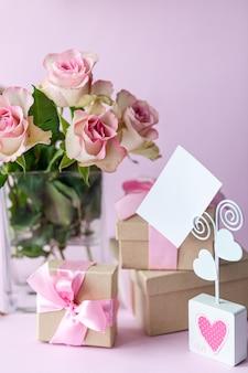 Geschenkbox mit einer rosa schleife und einer leeren karte.