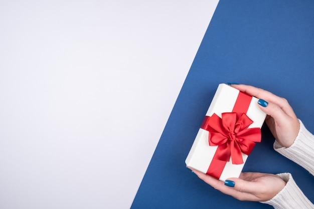 Geschenkbox mit einer roten schleife auf einem grauen und blauen hintergrund in den frauenhänden. platz für text