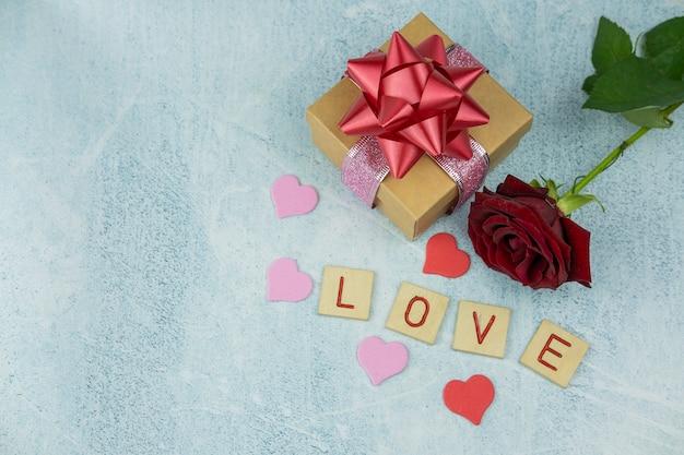 Geschenkbox mit einer roten schleife auf einem hintergrund von blumen rosen und bokeh mit dem text holzbuchstaben liebe für den feiertag valentinstag da