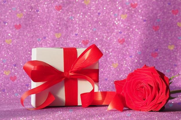 Geschenkbox mit einer roten schleife und einer roten rose auf einem lila glitzernden hintergrund