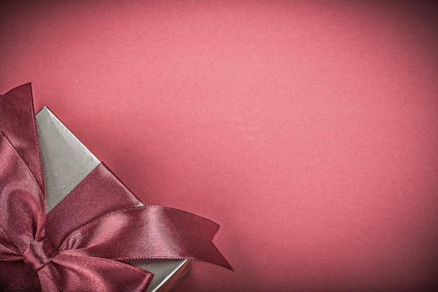 Geschenkbox mit gebundenem bogen auf rotem hintergrundfeiertagskonzept