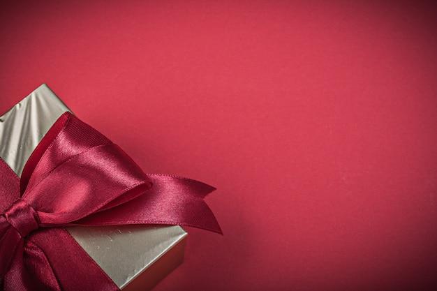 Geschenkbox mit gebundenem klebeband auf rotem hintergrundfeiertagskonzept