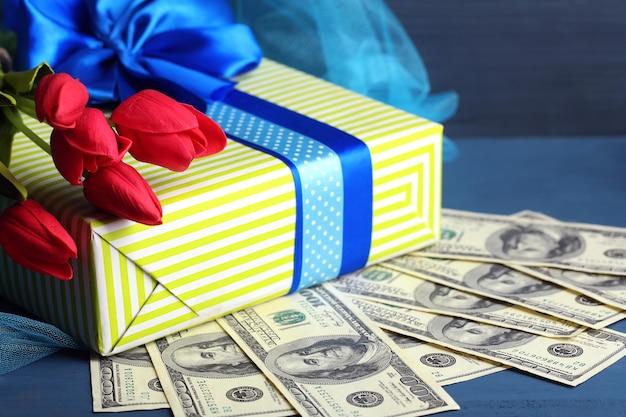 Geschenkbox mit geld und blumen auf farbiger holzoberfläche