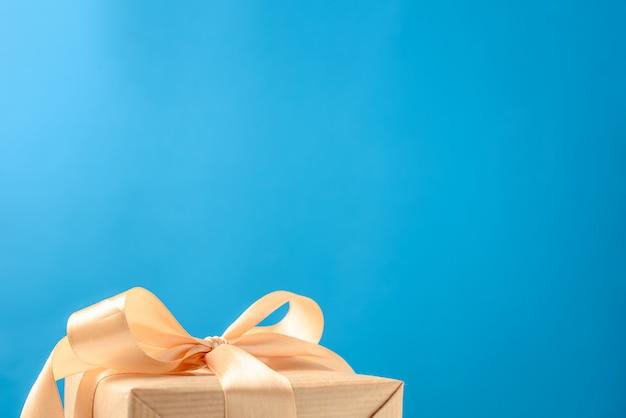 Geschenkbox mit goldbogen auf blau, kopienraum