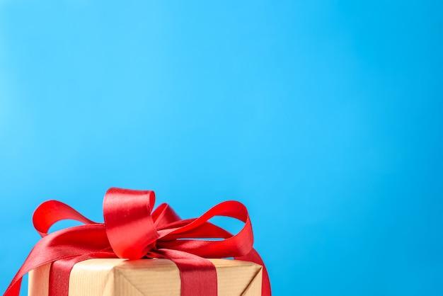 Geschenkbox mit goldbogen auf einem blauen hintergrund, kopienraum