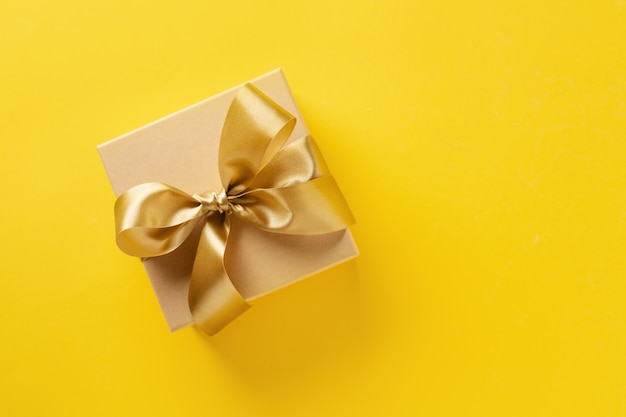 Geschenkbox mit goldenem band auf hellem hintergrund