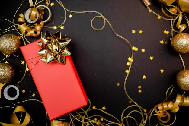 Geschenkbox mit goldenem bogen auf schwarzem hintergrund mit dekoration und scheinen