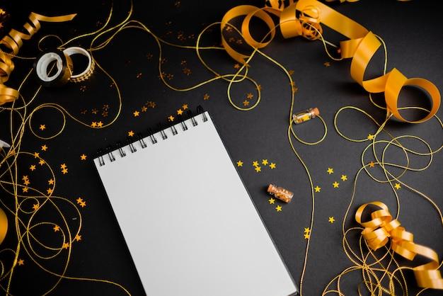 Geschenkbox mit goldenem bogen auf schwarzem hintergrund mit dekoration und sparklesew