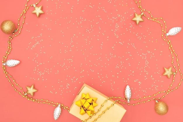 Geschenkbox mit goldenem stern, glocke und ball auf rosa lebendem korallenrotem hintergrund