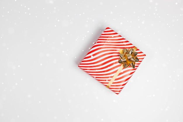 Geschenkbox mit goldener schleife auf weißer tafel mit festlichem goldenem glitzer