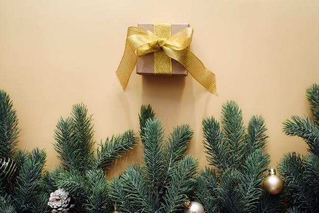 Geschenkbox mit goldschleife und weihnachtsbaumzweig mit kugeln auf beigem hintergrund.