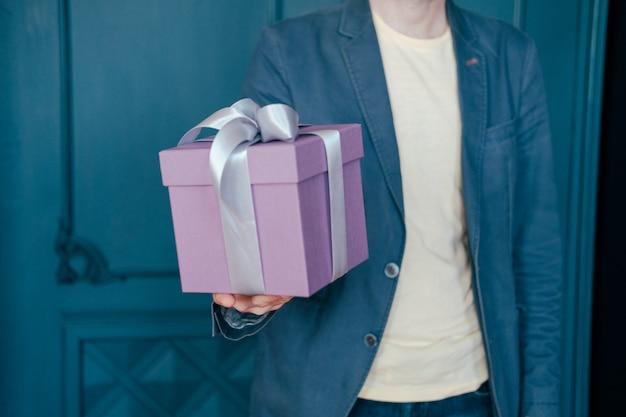 Geschenkbox mit grauem silbernem band in den händen des jungen attracrive mannes auf blauem hintergrund