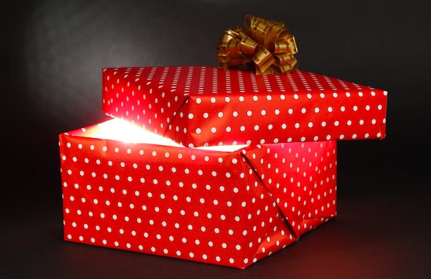 Geschenkbox mit hellem licht auf dunkelgrauem hintergrund