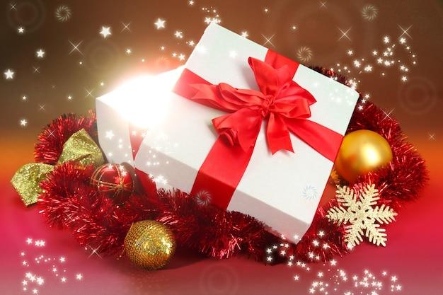 Geschenkbox mit hellem licht auf rotem hintergrund
