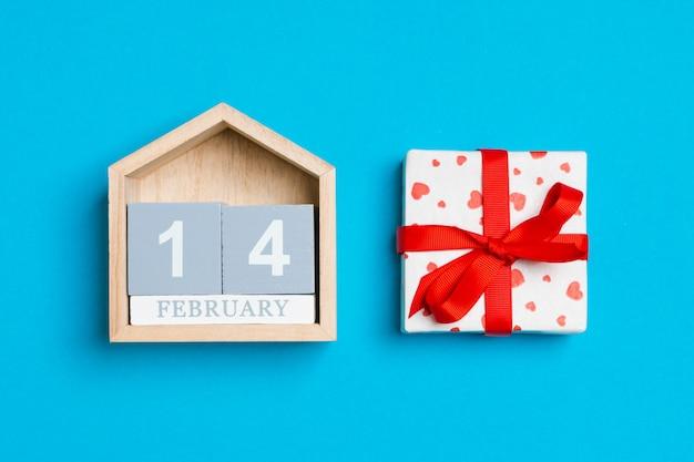 Geschenkbox mit herzen und hölzernem kalender auf blau