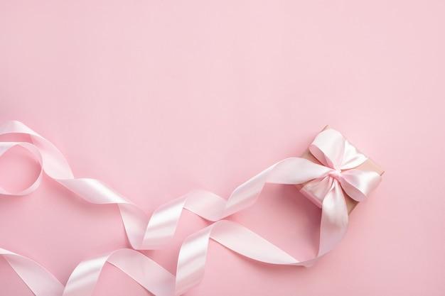 Geschenkbox mit langem band auf pastellrosa hintergrund. geschenk zum valentinstag