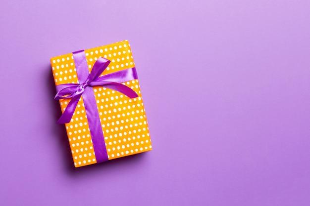 Geschenkbox mit lila schleife für weihnachten oder neujahr auf lila