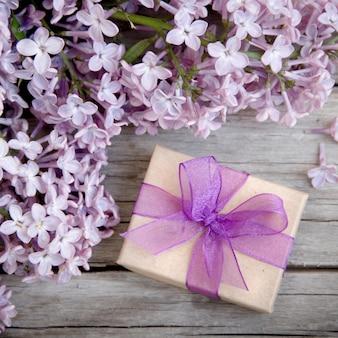 Geschenkbox mit lila schleife und flieder auf holz