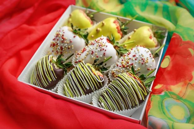 Geschenkbox mit nachtisch in form von den reifen erdbeeren bedeckt in der schokolade