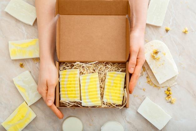 Geschenkbox mit naturseife in weiblichen händen. diy-seifen-set. viele verschiedene hausgemachte seifenstücke. hygieneartikel flach liegend.