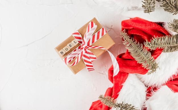 Geschenkbox mit noel-titel in der nähe von weihnachtsanzug und nadelzweigen