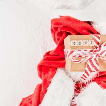 Geschenkbox mit noel-titel in der nähe von weihnachtsanzug