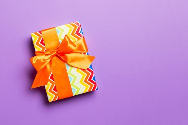 Geschenkbox mit orange bogen für weihnachten oder neujahr auf purpurrotem hintergrund, draufsicht mit kopienraum