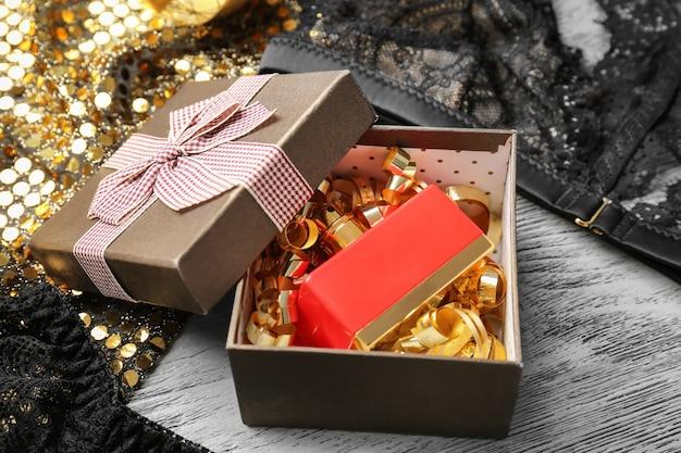 Geschenkbox mit parfümflasche auf tisch, nahaufnahme