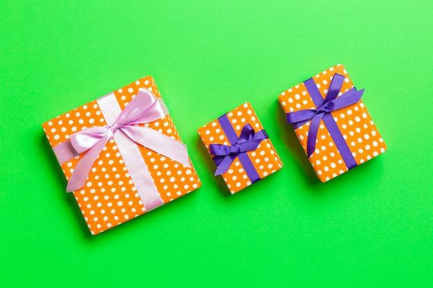 Geschenkbox mit purpurrotem und rosa bogen für weihnachten oder neujahr auf grünem hintergrund