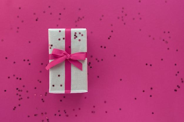 Geschenkbox mit rosa band und konfetti-dekorationen auf buntem hintergrund des pastellpapiers. flache lage, draufsicht, kopierraum