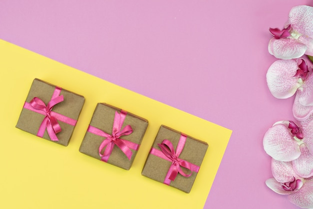 Geschenkbox mit rosa band und orchideenblüten