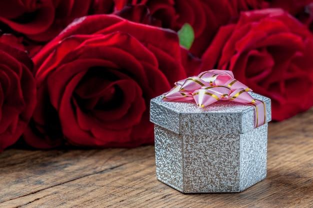Geschenkbox mit rosa band und roten rosen hinten