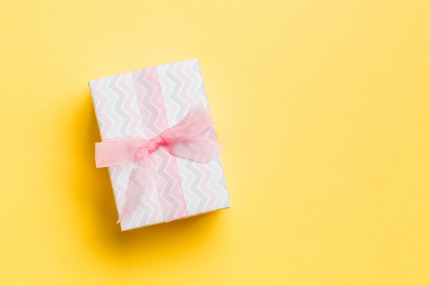 Geschenkbox mit rosa bogen für weihnachtstag auf gelb