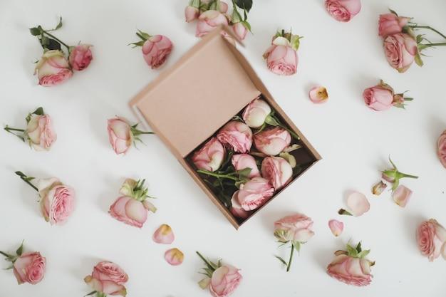 Geschenkbox mit rosa rosenblumen auf draufsicht des weißen hintergrunds