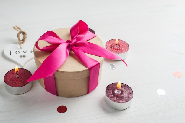 Geschenkbox mit rosa schleife und brennenden kerzen