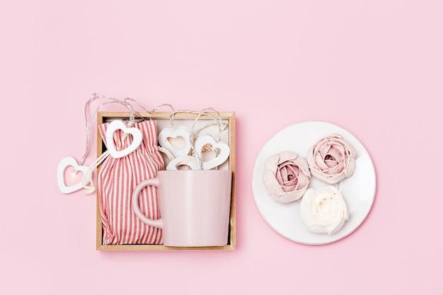 Geschenkbox mit rosa tasse, marshmallow und überraschung im textilbeutel