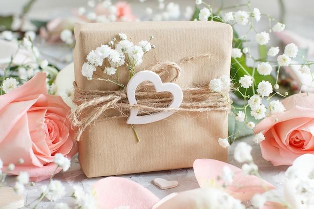 Geschenkbox mit rosen und kleinen weißen blumen auf grauem hintergrund