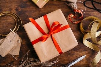 Geschenkbox mit rotem Band auf Tabelle