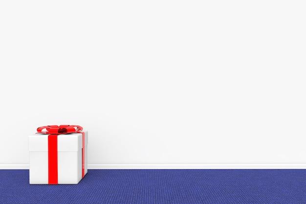 Geschenkbox mit rotem band gegen eine leere graue wand