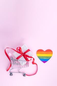 Geschenkbox mit rotem band im einkaufswagen und gemalter papier-lgbt-herzform auf rosa hintergrund