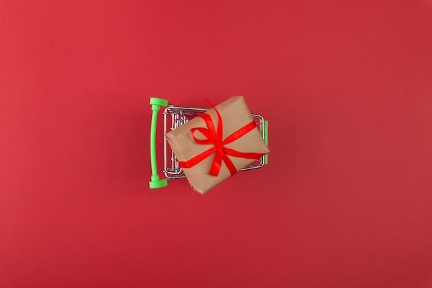 Geschenkbox mit rotem band im mini-einkaufswagen