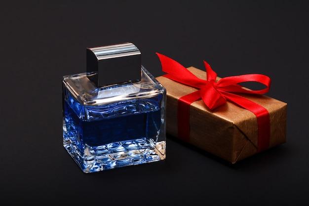 Geschenkbox mit rotem band und einer flasche parfüm auf schwarzem hintergrund gebunden. konzept zum feiertag.