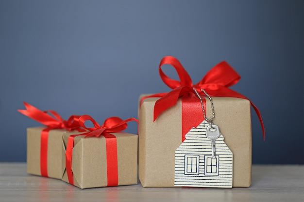 Geschenkbox mit rotem band- und hausmodell mit schlüsseln, neuem haus des geschenks und immobilienkonzept