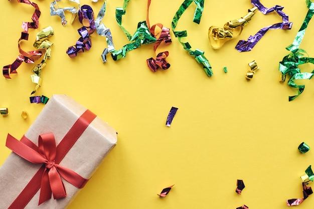 Geschenkbox mit rotem band und konfetti-dekorationen auf buntem hintergrund des pastellpapiers. feierkonzept. flache lage, draufsicht, kopierraum