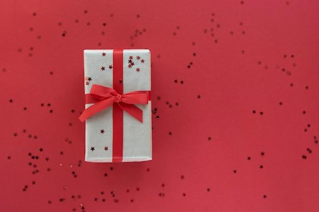Geschenkbox mit rotem band und konfetti-dekorationen auf buntem hintergrund des pastellpapiers. flache lage, draufsicht, kopierraum