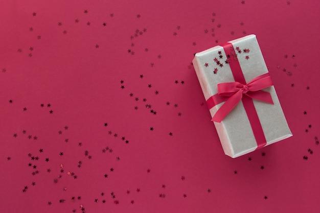 Geschenkbox mit rotem band und konfetti-dekorationen auf buntem hintergrund des pastellpapiers