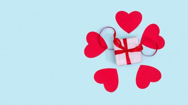 Geschenkbox mit rotem band und rotem papier lieben herzen herum auf einem blauen hintergrund