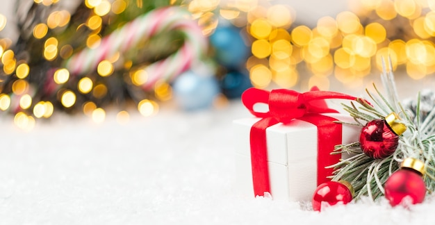 Geschenkbox mit rotem band und unscharfem weihnachtsbaum