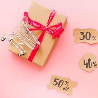 Geschenkbox mit rotem bogen nahe einkaufslaufkatze